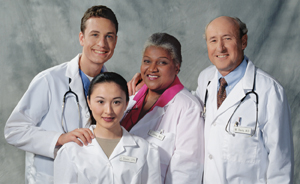 Group of four health care providers smiling.