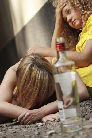 Two teen girls passed out with empty bottle of alcohol.