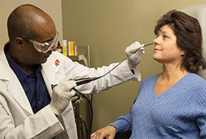 Healthcare provider preparing to insert endoscope into woman's nose.