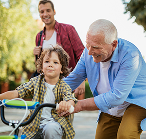 Image of Grandfather Helping Grandson to Ride a Bike